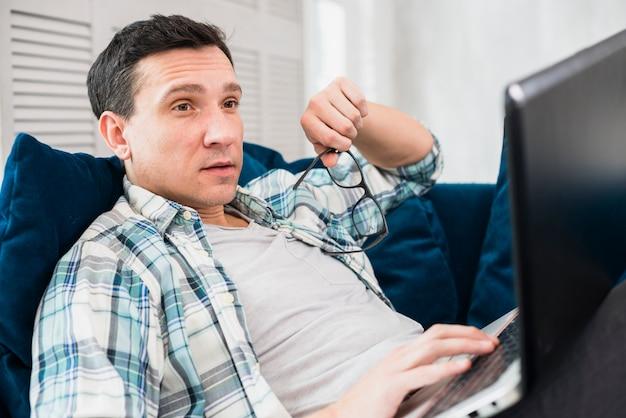 Zdziwiony mężczyzna używa laptop na kozetce