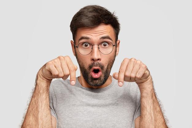 Zdziwiony mężczyzna wskazuje palcami wskazującymi w dół, zauważa coś zaskakującego, trzyma usta otwarte