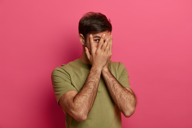 Zdziwiony mężczyzna zakrywa twarz rękami, patrzy przez palce