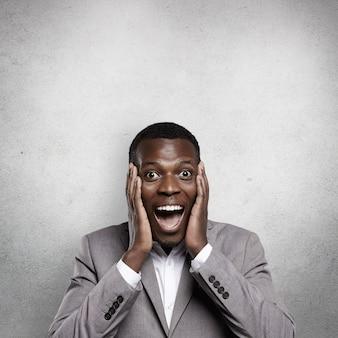 Zdziwiony młody afrykański biznesmen ubrany w oficjalny strój, wyglądający na podekscytowanego i zszokowanego, trzymający ręce na policzkach, krzyczący z szeroko otwartymi ustami, zdumiony dochodową ofertą biznesową lub wielką wyprzedażą