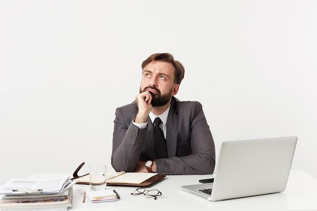 Zdziwiony młody brodaty brunet z krótką fryzurą, ubrany w formalne ubrania i zegarek na rękę, siedząc przy stole z nowoczesnym laptopem i notatkami roboczymi na białej ścianie