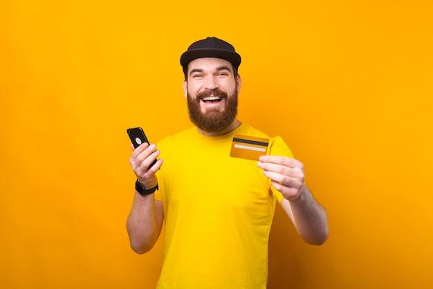 Zdziwiony młody brodaty mężczyzna za pomocą karty kredytowej i smartfona na żółtym tle