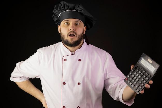 Zdziwiony młody brodaty szef kuchni w mundurze trzyma kalkulator pokazuje wyniki obliczeń