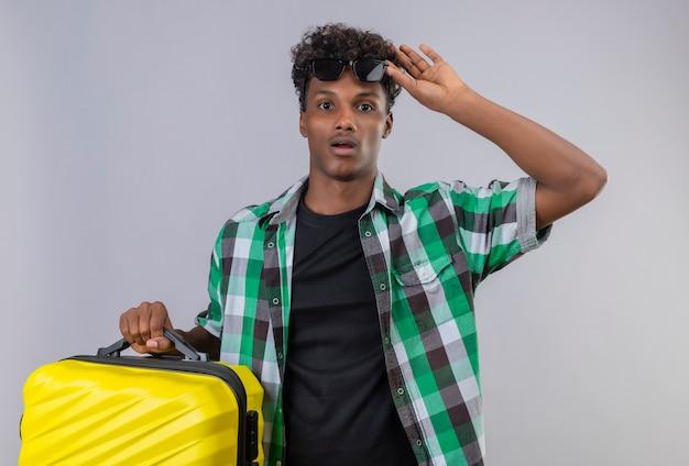 Zdziwiony młody człowiek afroamerykański podróżnik trzymający walizkę zdejmujący okulary przeciwsłoneczne ze zdumienia