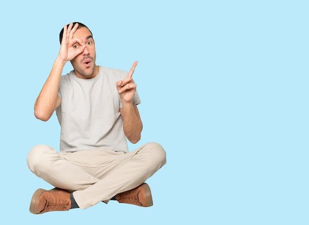 Zdziwiony młody człowiek, który używa rąk jak lornetki