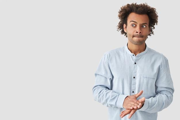 Zdziwiony młody człowiek rasy mieszanej gryzie usta, ma chrupiące włosy, trzyma ręce razem, wygląda dziwnie na bok, ubrany w modną koszulę, pozuje na białej ścianie