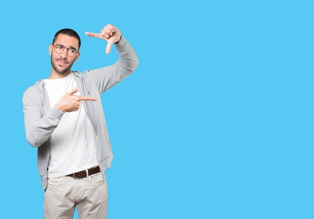 Zdziwiony młody człowiek robi gest robienia zdjęcia rękami