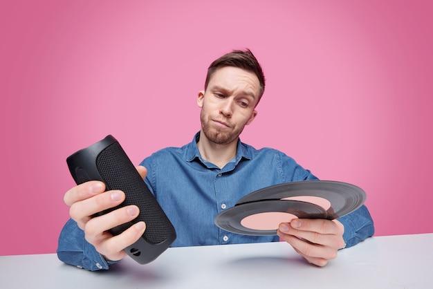 Zdziwiony młody człowiek w dżinsowej koszuli trzymający kolumnę muzyczną i dwie płyty vynil, wybierając to, czego słuchać w wolnym czasie