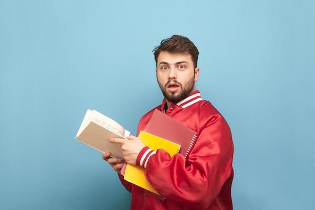 Zdziwiony młody człowiek z brodą i książkami w rękach, ubrany w czerwoną kurtkę