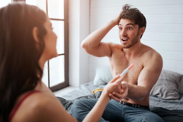 Zdziwiony młody mężczyzna patrzy na kobietę i trzyma ją za rękę z testem ciążowym. on jest szczęśliwy. siedzą na łóżku. szczęśliwa kobieta patrzy na niego.