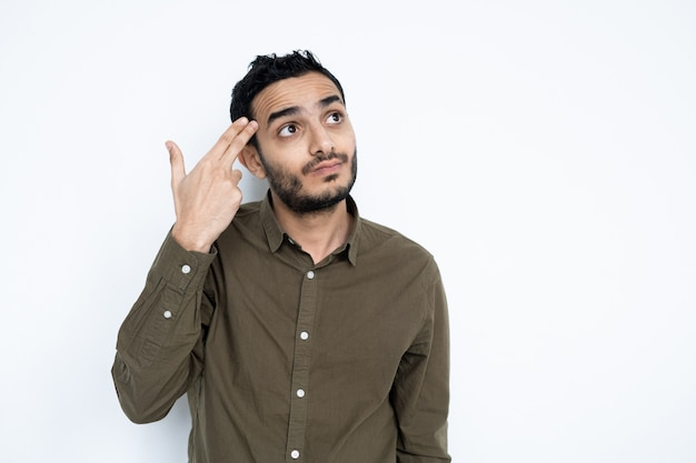 Zdziwiony młody mężczyzna w codziennym stroju, trzymający dwa palce za głowę, patrząc w górę w odosobnieniu