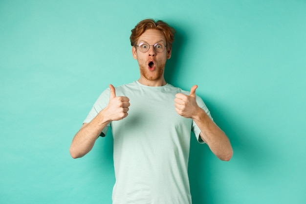 Zdziwiony młody mężczyzna z rudymi włosami i brodą, w okularach z t-shirtem, pokazujący kciuki do góry i sapiąc z zachwytu, sprawdzający niesamowitą ofertę promocyjną, turkusowe tło.
