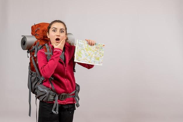Zdziwiony młody podróżnik z dużym plecakiem trzymającym mapę na szaro