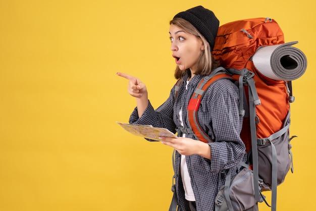 Zdziwiony młody podróżnik z plecakiem trzymającym mapę