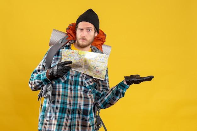 Zdziwiony młody turysta w skórzanych rękawiczkach i plecaku trzymającym mapę