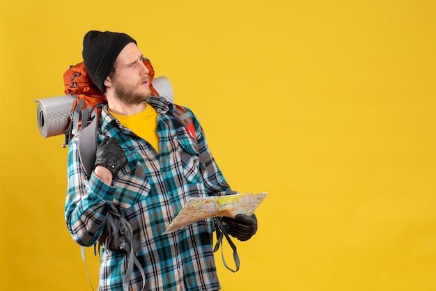Zdziwiony młody turysta ze skórzanymi rękawiczkami i plecakiem trzymającym mapę