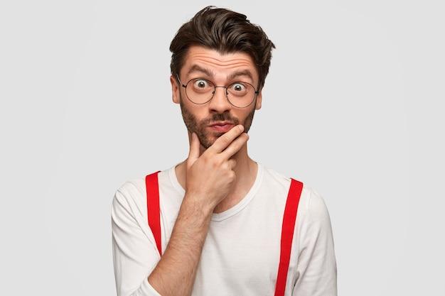 Zdziwiony modny mężczyzna zastanawia się nad nowościami ze sfery biznesowej, trzyma podbródek, zaskakuje wyrazem twarzy