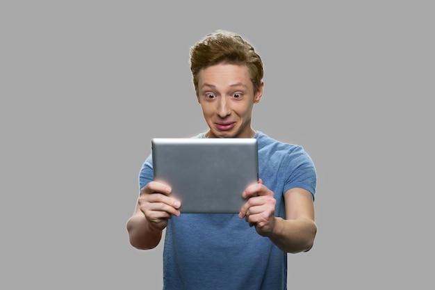 Zdziwiony nastolatek chłopiec patrząc na cyfrowy tablet. shoked teen guy za pomocą komputera typu tablet na szarym tle.