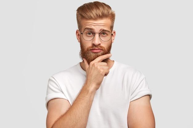 Zdziwiony niezdecydowany rudowłosy mężczyzna trzyma brodę i unosi brew z bezmyślnym wyrazem twarzy