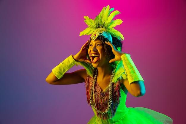 Zdziwiony. piękna młoda kobieta w karnawałowym, stylowym stroju maskarady z piórami tańczącymi na gradientowym tle w neonowym kolorze. koncepcja obchodów świąt, świąteczny czas, taniec, impreza, zabawa.