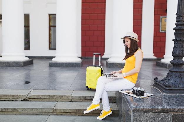 Zdziwiony podróżnik turysta kobieta z walizką siedzi na schodach przy użyciu pracy na komputerze typu laptop w mieście na świeżym powietrzu. dziewczyna wyjeżdża za granicę na weekendowy wypad. koncepcja życia podróż turystyka.