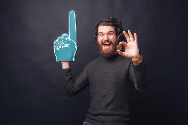 Zdziwiony przystojny brodaty mężczyzna pokazujący bitcoin i wskazujący rękawicą wentylatora