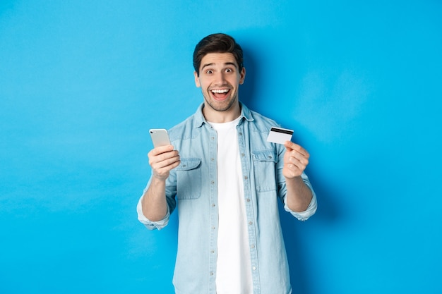 Zdziwiony przystojny mężczyzna robi zakupy w internecie, trzymając telefon komórkowy i kartę kredytową, uśmiechając się, płacąc za zakupy w internecie, stojąc nad niebieską ścianą