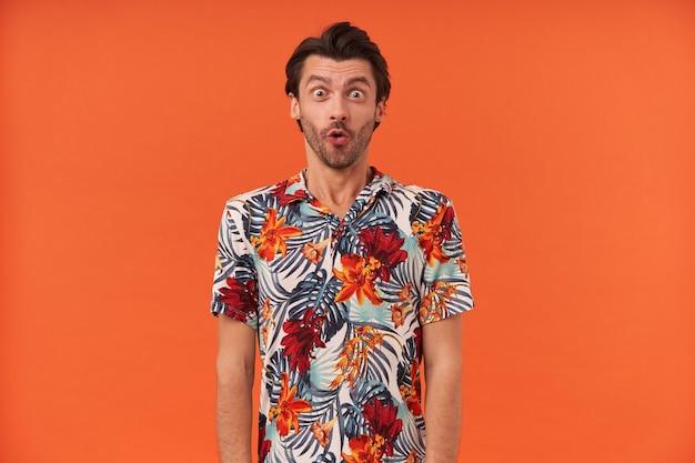 Zdziwiony, przystojny młody mężczyzna z włosiem w hawajskiej koszuli stoi i czuje się zaskoczony