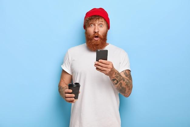 Zdziwiony przystojny rudowłosy facet pozuje z telefonem