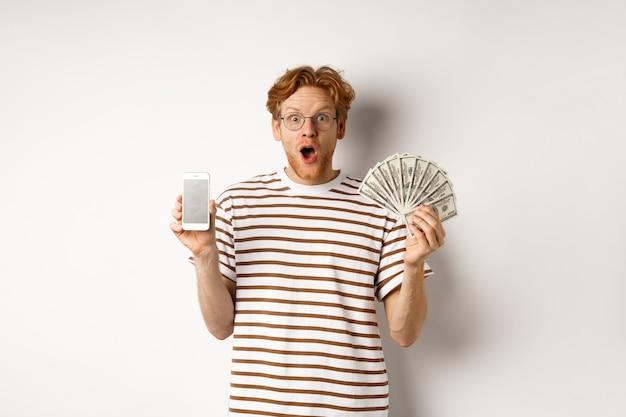 Zdziwiony rudy mężczyzna pokazujący aplikację na smartfonie na pustym ekranie i pieniądze, wygrywając nagrodę pieniężną w internecie, stojąc na białym tle.