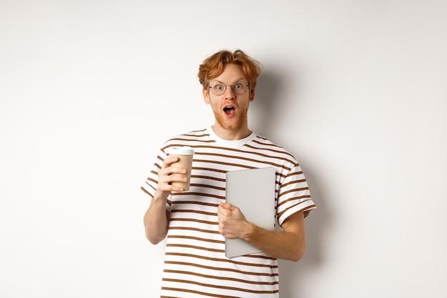 Zdziwiony rudy mężczyzna rozmawia ze współpracownikami na przerwie na kawę, trzymając kubek i laptop, wpatrując się zdziwiony w kamerę, białe tło.