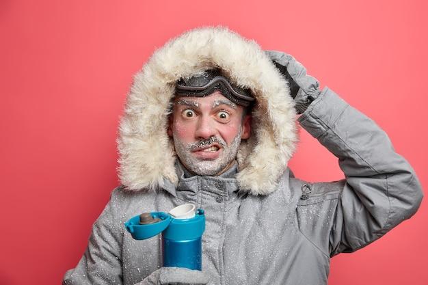 Zdziwiony turysta ma zamarzniętą twarz zszokowaną zimnem podczas wyprawy, ubrany jest w ciepłą kurtkę i gogle narciarskie pije gorący napój.