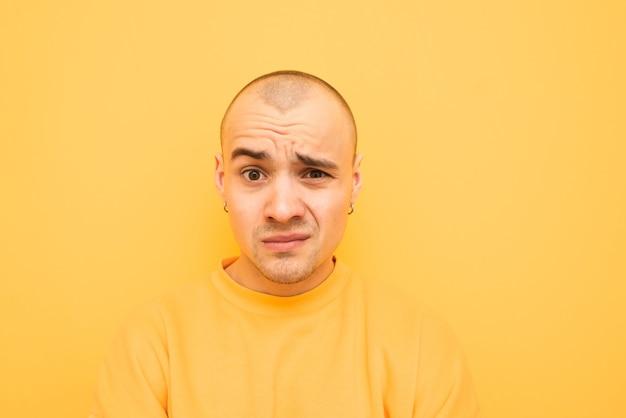 Zdziwiony zabawny facet jest izolowany na żółto