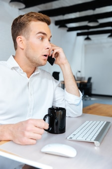 Zdziwiony zaskoczony młody biznesmen rozmawia przez telefon komórkowy i pije kawę w biurze