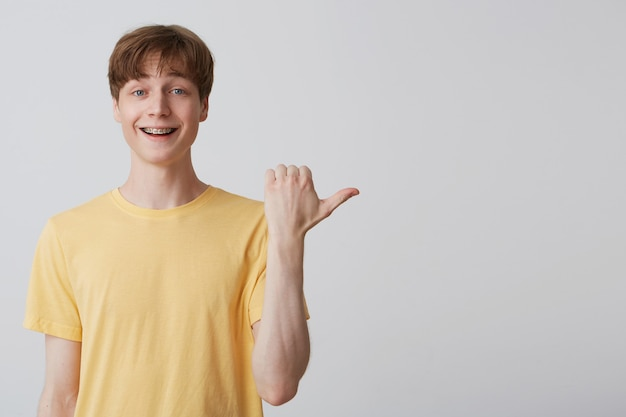 Zdziwiony zdenerwowany młody student wskazał kciukiem na białą pustą kopię, szeroko otworzył usta z zaskoczonym wyrazem twarzy