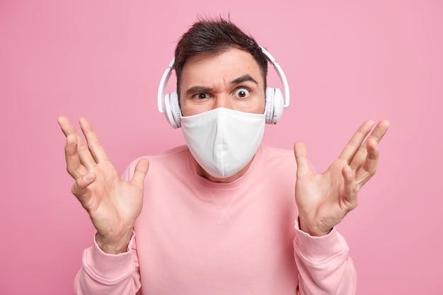 Zdziwiony, zdezorientowany mężczyzna unosi dłonie, słucha muzyki przez białe słuchawki bezprzewodowe, unosi brwi, nosi maskę ochronną, aby zapobiec koronawirusowi, ubrany niedbale