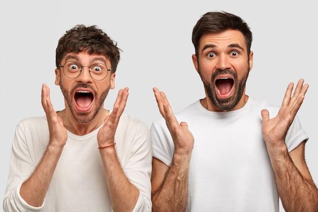 Zdziwiony zdumiony radosny dwaj panowie ze zdumienia wykrzykują, czynnie gestykulują, z opuszczoną szczęką, nie mogą uwierzyć w taki sukces, ubrani niedbale, odizolowani na białej ścianie. koncepcja języka ciała