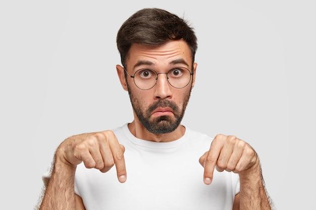 Zdziwiony, zdziwiony nieogolony młody człowiek z ciemnym zarostem, wskazuje w dół dwoma palcami wskazującymi