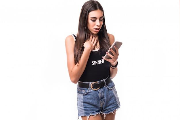 Zdziwiony żeński brunetka model w cajgów skrótach odizolowywających