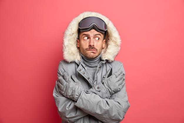 Zdziwiony zmarznięty mężczyzna krzyżuje ręce i próbuje się ogrzać, drży z zimna podczas śnieżnej, niskiej temperatury, nosi ciepłe zimowe rękawiczki kurtki i gogle narciarskie, trzęsąc się z mrozu w mroźny dzień
