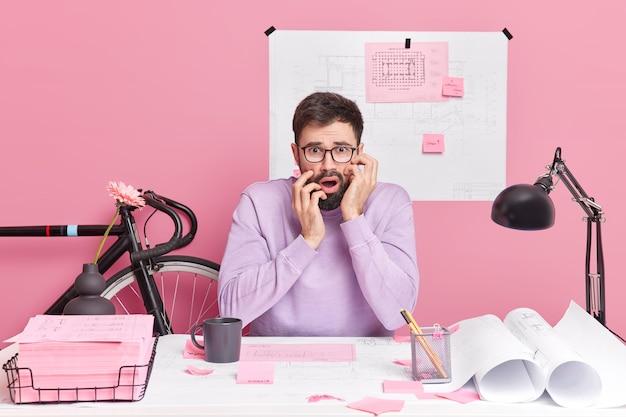 Zdziwiony, zszokowany brodaty mężczyzna, architekt pracuje w biurze z planami pozuje na pulpicie, ubrany niedbale
