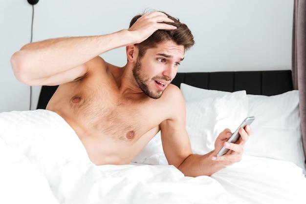 Zdziwiony, zszokowany młody człowiek korzystający z telefonu komórkowego w łóżku rano