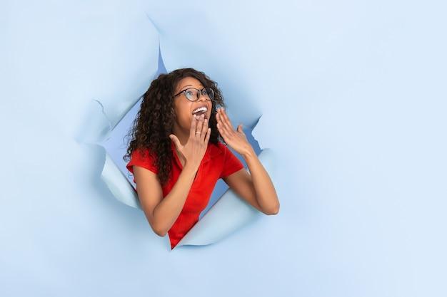 Zdziwiony zszokowany zdumiony wesoła afroamerykanka w rozdartym niebieskim kolorze