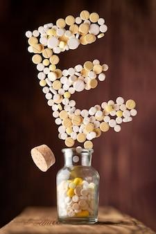 Ze szklanego słoika wylatują różne pigułki w kształcie litery e na drewnianej powierzchni