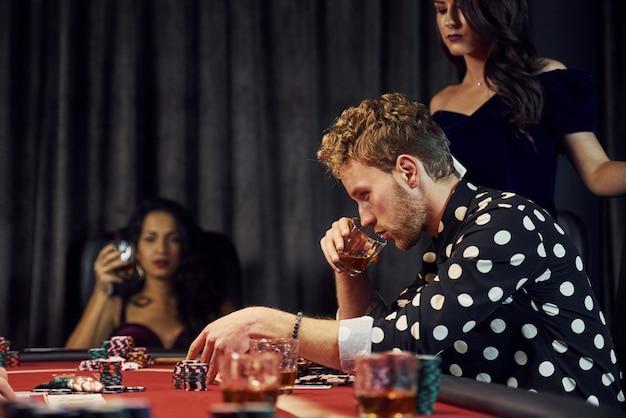 Ze szklankami napoju. grupa eleganckich młodych ludzi grających razem w pokera w kasynie