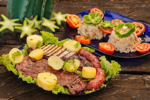 Żeberka i kiełbaski z mięsa koziego pieczone w towarzystwie rubacao brazylijskiego północno-wschodniego jedzenia