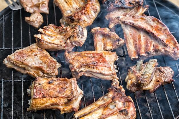 Żeberka jagnięce gotowane są na okrągłym grillu z przyprawami.
