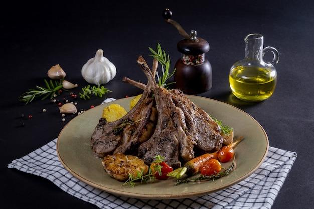 Żeberka jagnięce grillowane na desce do krojenia z pieczonymi warzywami