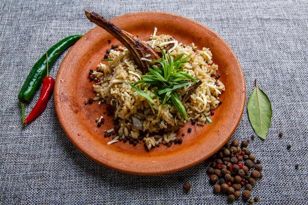 Żeberka jagnięce z ryżem na glinianym talerzu. teksturowane szare płótno. obok talerza strąki pieprzu i groszek, liść laurowy. kuchnia gruzińska.