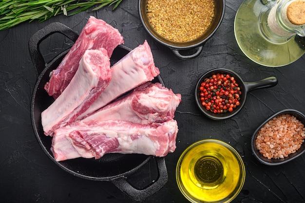 Żeberka surowe z zestawem rozmarynu i warzyw, z miodem, na patelni żeliwnej, na stole z czarnego kamienia, widok z góry na płasko
